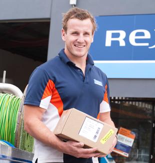Rexelin työntekijä kantaa pakettia